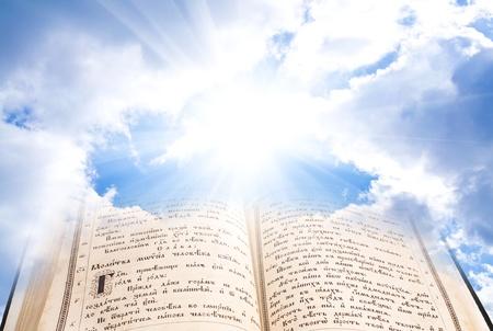Öffnen Sie Bibel mit mystischen Strahlen gegen Wolken