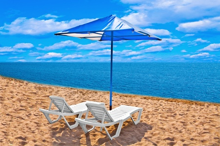 beach with chaise lounges and umbrella photo