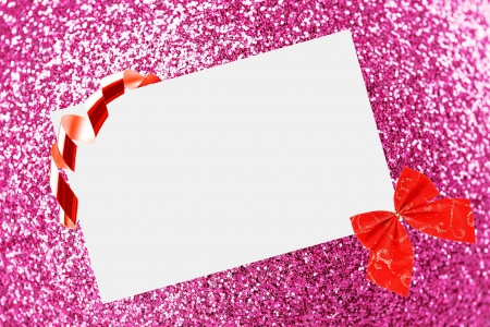 Christmas sheet of paper with bow and ribbons on pink defocused background