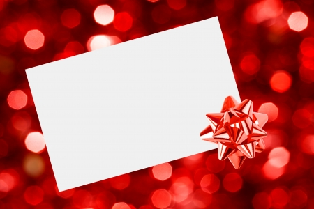 Christmas sheet of paper with bow on red defocused background photo
