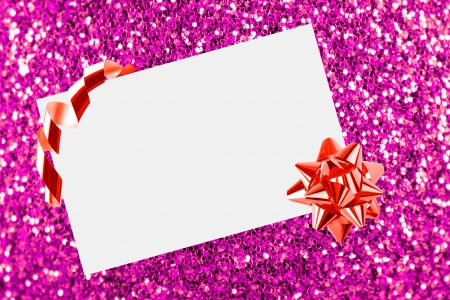 Christmas sheet of paper with bow on pink defocused background photo