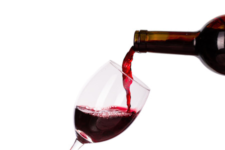 Red wine being poured into wine glass isolated on the white