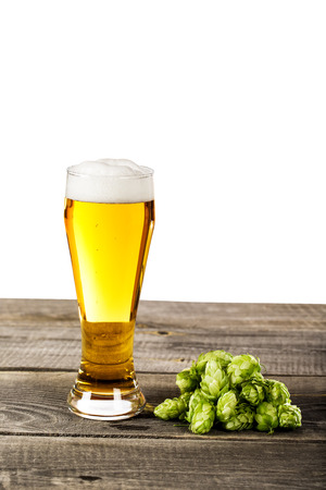 beer glass with foam and hops isolated on a vintage wooden table Stock Photo