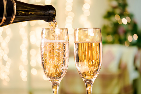 champagne flute: Two Champagne Glass On Defocused Background Living Room With Christmas Tree Stock Photo