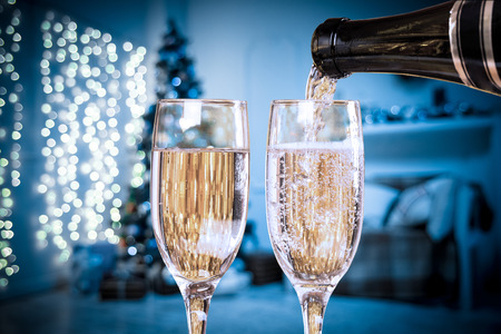 hearthside: Two Champagne Glasses On Defocused Background Living Room With Christmas Tree. Blue toned Stock Photo