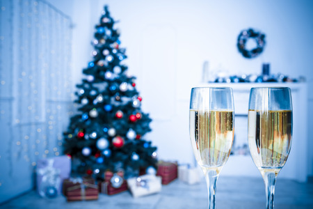 hearthside: Two Champagne Glass On Defocused Background Living Room With Christmas Tree. Blue toned