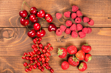 Collection of cherries, strawberries, red currants, raspberries on wood background