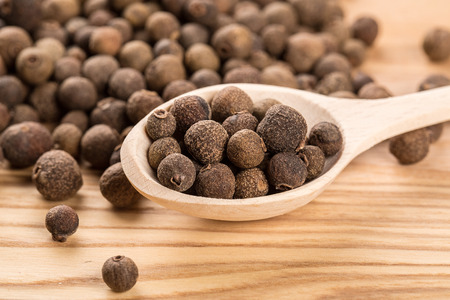 allspice: allspice in a wooden spoon on the wood table Stock Photo