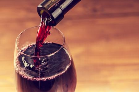 Strömender Rotwein in das Glas gegen Holzuntergrund