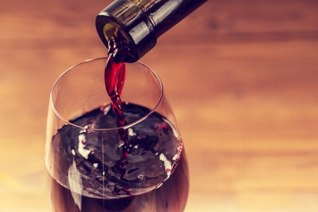 pouring wine: Pouring red wine into the glass against wooden background