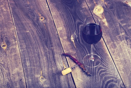 glass bottle: Pouring red wine into the glass against wooden background