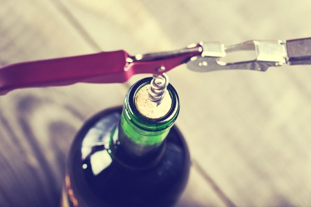 wine testing: Bottle of wine with corkscrew on wooden background Stock Photo