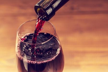 bottle liquor: Verter el vino tinto en el vaso contra el fondo de madera