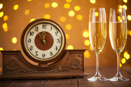 past midnight: Christmas card. Glasses of champagne on New Years Eve on the stand an ancient clock