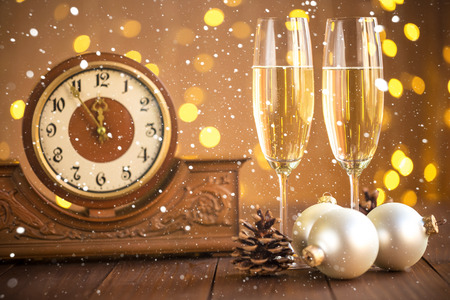 celebrate year: Christmas card. Glasses of champagne on New Years Eve on the stand an ancient clock with snow