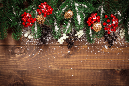red christmas backgrounds: Beautiful Christmas background with the branches of the Christmas tree and snow on wooden background. View with copy space Stock Photo