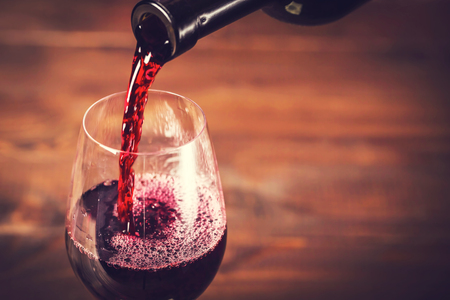 bebiendo vino: Verter el vino tinto en el vaso contra el fondo de madera