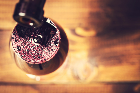 Pouring red wine into the glass against wooden background. Soft focus Stock Photo