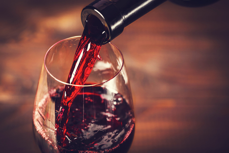 Pouring red wine into the glass against wooden background Stok Fotoğraf - 51975924