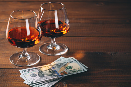 Two glasses of cognac with wad of money on the wooden table.