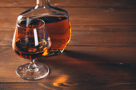 cognac: Glasses of cognac and bottle on the wooden table.