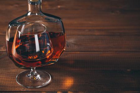 alcool: Verres de cognac et une bouteille sur la table en bois.
