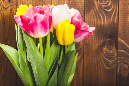 valentine card: Bouquet Of Tulips In Front Of Spring Scene On The Wooden Background. A bouquet of flowers for March 8, or Valentines day