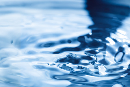 Falling droplets and Splash of water on blue surface Stock Photo