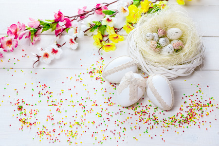 Beautiful Easter background with flowers and nest with eggs on white painted boards