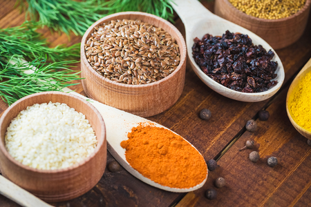variability: Beautiful colorful spices in wooden spoons and bowls on an old wooden brown table with green dill