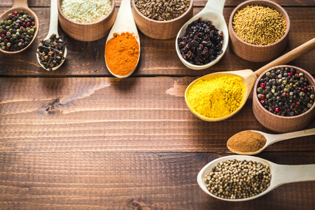 variability: Beautiful colorful spices in wooden spoons and bowls on an old wooden brown table.