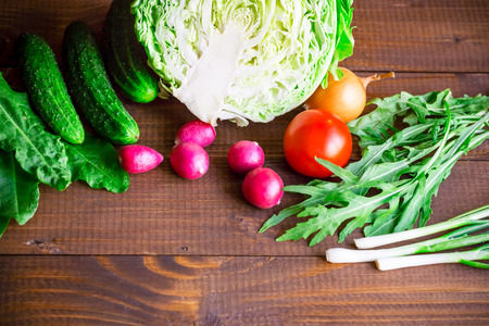 substrate: background with old brown boards with fresh healthy vegetables, green onion, radish, cucumber, arugula and cabbage. Empty space for text. Stock Photo