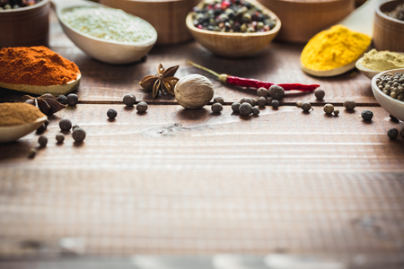 variability: Beautiful colorful spices in wooden spoons on an old wooden brown table. Free space for your text Stock Photo