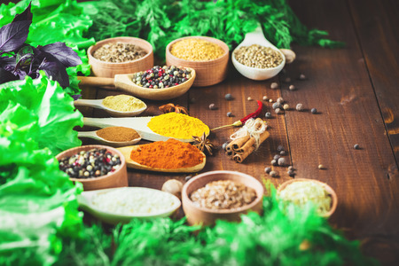 variability: Beautiful colorful spices in wooden spoons and bowls with lettuce, dill and Basil on an old wooden brown table. Free space for your text Stock Photo