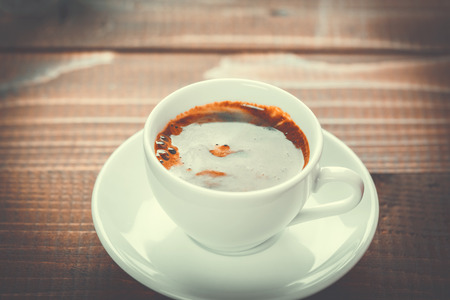 crema: Beautiful background with a hot Cup of coffee with Crema on wooden background