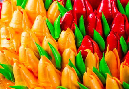 adorned: Background beautiful birthday cake adorned with edible red and orange tulips