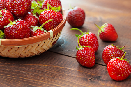 osier: Very beautiful background with fresh strawberries in a wicker round osier basket on old brown wooden background