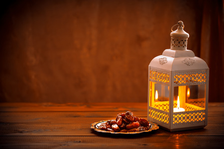 Beautiful background with a shining Fanus lantern and dried dates on a tray.