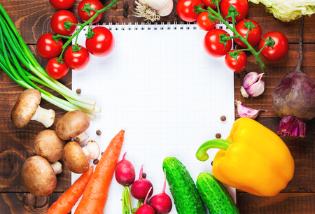 organic peppers sign: the frame of different vegetables and mushrooms with a white sheet of paper on the old brown boards with free space Stock Photo