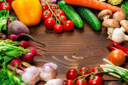 organic peppers sign: the frame of different vegetables and mushrooms on the old brown boards with free space Stock Photo