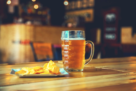 unbottled: A fresh glass of cold light beer and potato chips on the wooden bar counter in pub with free space for your text. Beautiful background of the Oktoberfest.