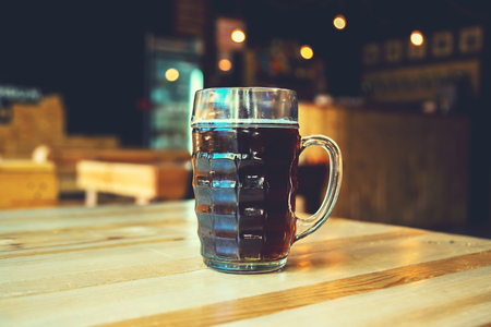 A chilled glass of fresh dark beer on the wooden bar counter in pub with free space for your text. Beautiful background of the Oktoberfest. Stock Photo