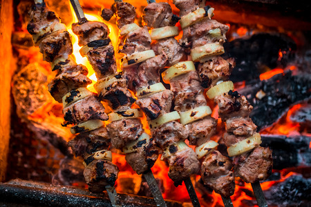 kebob: Barbecue pork kebabs on the hot grill close-up. Flames of fire and coals in the background