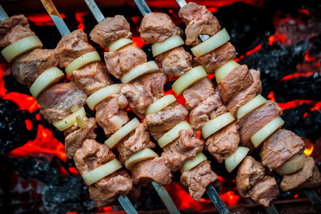 barbequing: Barbecue pork kebabs on the hot grill close-up. Flames of fire and coals in the background