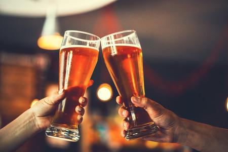 Dos amigos brindando con vasos de cerveza ligera en el pub. Fondo hermoso de la Oktoberfest. grano fino. Enfoque suave. DOF bajo Foto de archivo - 61334957