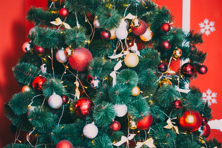 hearth and home: Beautiful decorated Christmas tree with red and goldish baubles and garland, in the new-year background. The idea for postcards. Soft focus. Shallow DOF Stock Photo