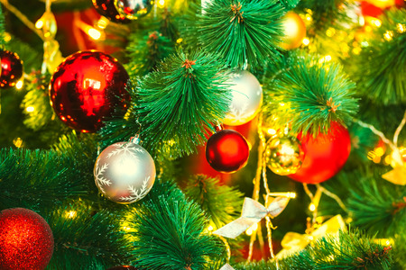Beautiful decorated Christmas tree with red and goldish baubles and garland, in the new-year background. The idea for postcards. Soft focus. Shallow DOF Stock Photo