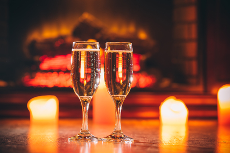 Beautiful Two glasses of champagne on blurred background with candles and a fireplace. The idea for postcards. Soft focus. Shallow DOF