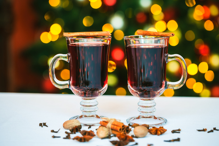 punch spice: Beautiful Two glasses of mulled wine on bokeh background decorated Christmas tree. The idea for postcards. Soft focus. Shallow DOF