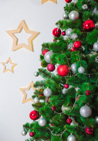 hearth and home: Closeup of Christmas-tree background in the living room of the house with glowing stars on the wall Stock Photo